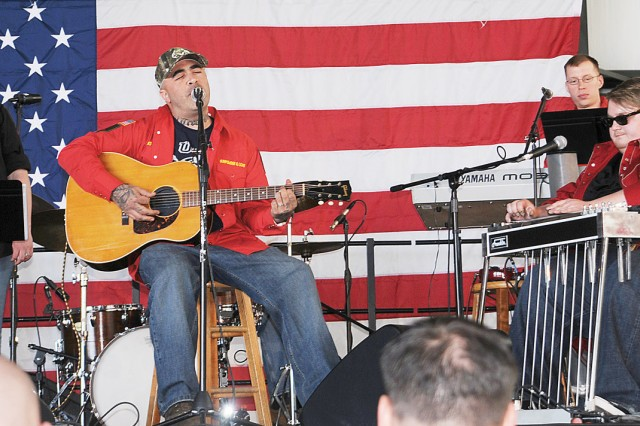 """Aaron Lewis, solo country music singer and lead vocalist with the rock band, Staind, center, performs the song, """"Tangled Up in You,"""" with Tiana Navarro, lead singer with the 1st Infantry Division Band's """"Gunpowder and Lead,"""""""