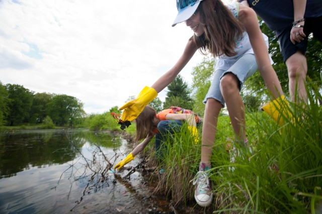 Willmary Anderson, 12, a sixth-grader at MacArthur Middle School, tries not to fall into Burba Lake as she retrieves plastic from the water's edge Saturday during the Enlisted Spouses Club's annual Fort Meade Cleanup Day. Forty people
