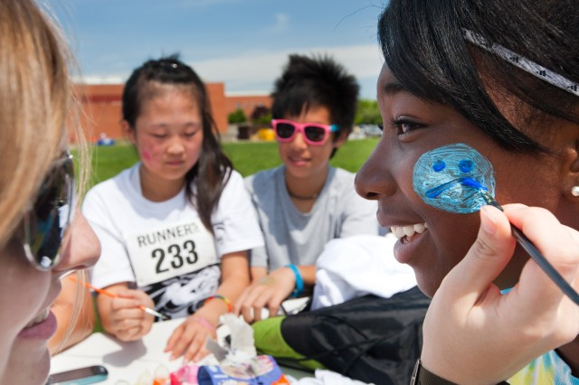 Gabriella Damewood, 17, paints the cheek of fellow Meade High student Yamaila Bangura, 16, during Meade Madness held Saturday at the school. More than 450 students and parents of the Meade High feeder schools attended the annual event.