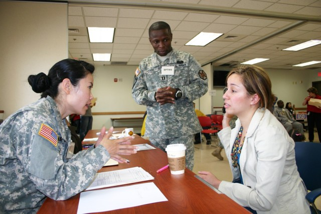 Spc. Yingmei Yang from Delta Detachment, 175th Finance Company, attempts to help a Spanish-speaking spouse in need of money as Capt Leon Cook, U.S. Army Garrison Red Cloud Directorate of Plans, Training, Mobilization and Security, monitors the quality of