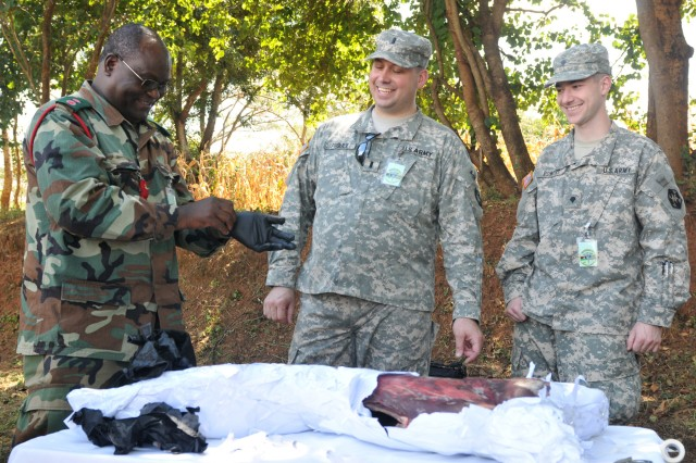 1st Lt. Jason J. Proulx (center) and Spc. Ian P. Powers, 399th Combat Support Hospital laugh with a Malawi Defence Soldier as he prepares to insert a surgical needle into a goat cadaver during Combat Life Saver training at Kamuzu Barracks, Lilongwe,