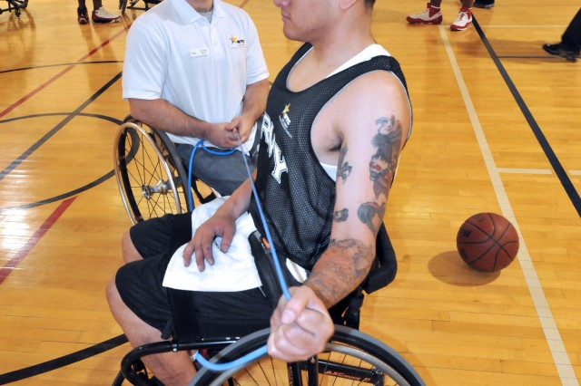 Sgt. Lester Perez, Warrior Transition Unit, Joint Base Lewis-McChord, Wash., is assisted with stretching exercises after a team workout for the Warrior Games in Colorado Springs, Colo.