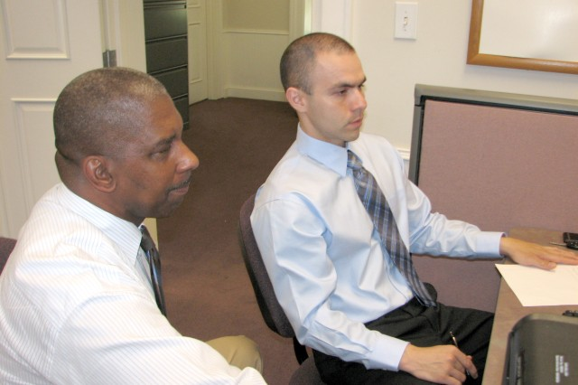 Alfonso Lewis (left), Army Community Service (ACS) employment readiness program manager, helps Sgt. Jorge Pena, human resource sergeant, 3rd Military Police Group, Criminal Investigation Division, Fort Gillem, with his job search during a employment