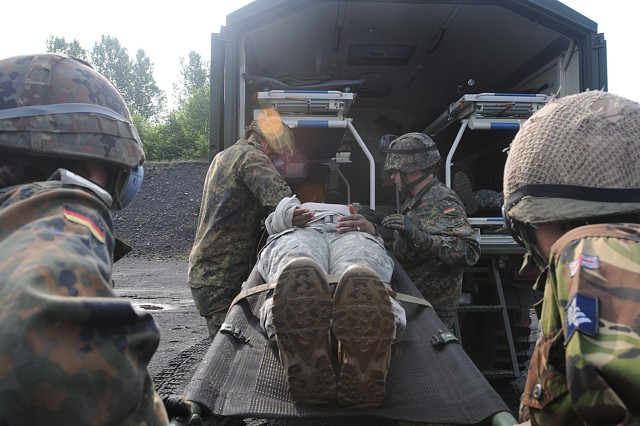German and British Soldiers load a simulated casualty into a field ambulance during a joint medical training exercise in Hamm, Germany, May 12, 2011.