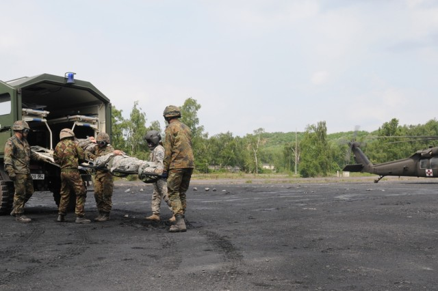 American, British and German Soldiers load a simulated casualty into a field ambulance during a joint medical training exercise in Hamm, Germany, May 12, 2011.