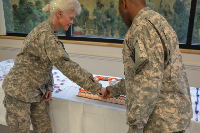 Col. Mary Link, Commander Detachment 25, and CSM Robert Peyton, III, Detachment Command Sergeant Major, cut the cake to start the reception