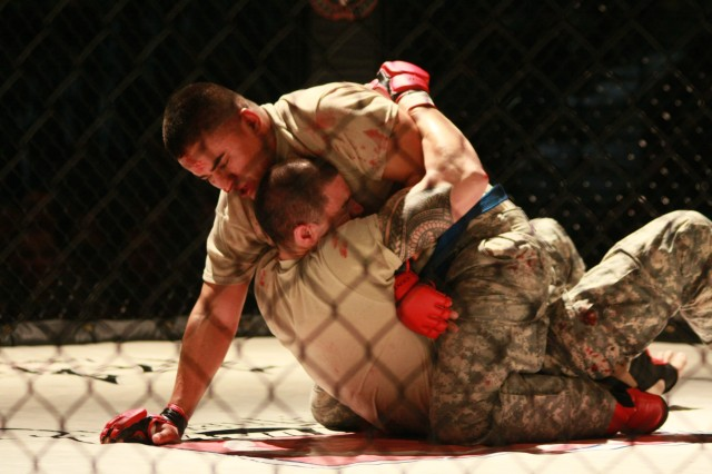 Dripping sweat and with blood smeared messily on their uniforms, two Joint Base Lewis-McChord, Wash., Soldiers reach exhaustion in the ring May 5 during the second-annual JBLM Combatives Tournament, which lasted May 2-5. Even though not every competitor
