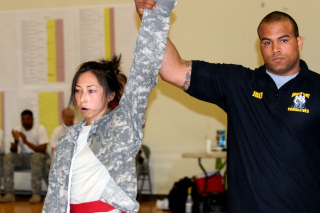 Pfc. Jennifer Jones, a Soldier with 2nd Brigade, 2nd Infantry Division, has her hand held high May 4 after dominating her opponent during the second annual Joint Base Lewis-McChord Combatives Tournament, held May 2-5 at Soldiers Field House. Jones went