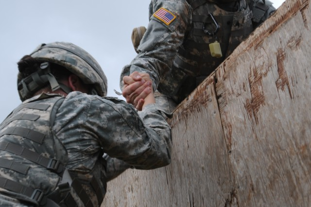 SCHOFIELD BARRACKS, Hawaii - (May 4, 2011) - 311th Signal Command's 2011 Non-Commissioned Officer of the Year Sgt. Harold Stoker helps a fellow Soldier over a wall during the week of competition. (photo by Staff Sgt. Crista Yazzie, 311th Public