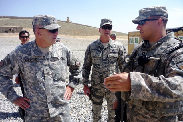 Brig. Gen. Tom Cosentino, deputy commander, Regional Support, NTM-A /CSTC-A (left), receives an initial briefing from Capt. David Dietz, the contracting officer's representative for the Regional Support Command-Capital, prior to the flag-raising