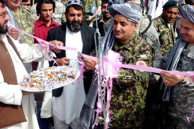Afghan Maj. Gen. Qadam Shah, 111th Capital Division commander, cuts the ribbon to symbolize the Afghan control of Forward Operating Base Deh Sabz, Afghanistan, during a flag-raising ceremony May 12, 2011, to mark the completion of the base near the