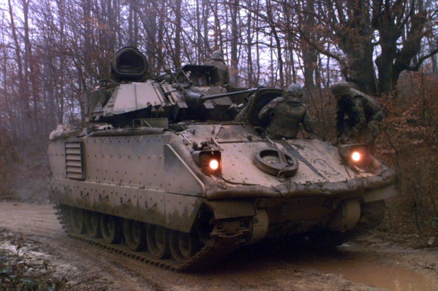 The crew of a Quarterhorse M3A2 cavalry fighting vehicle halts along a mud road during a patrol in Bosnia in February 1996.