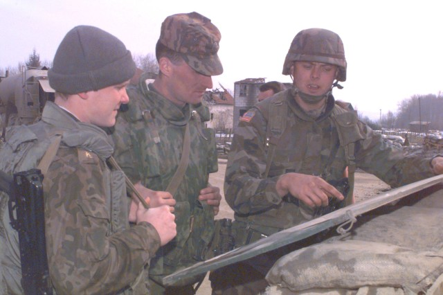 Quarterhorse scout platoon leader First Lieutenant Randy Ellsworth confers with Russian paratroopers prior to a combined patrol in Bosnia in February 1996.