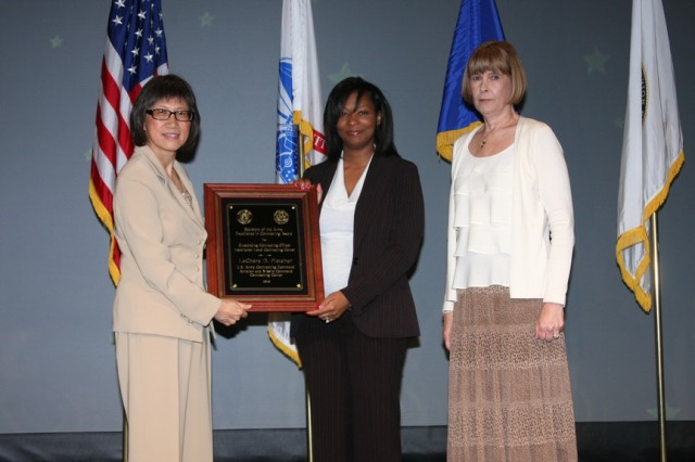 LeChara D. Fletcher (middle), Aviation and Missile Command, Contracting Center, Redstone Arsenal, accepts the award for Outstanding Contracting Officer Installation Level Contracting - Center at the Secretary of the Army Awards for Excellence in