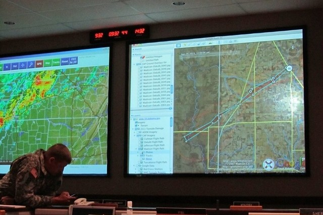 A view of the main screens in the Madison County Emergency Management Agency's emergency operations center. On the left, real-time weather and on the right, a preliminary damage track derived from Civil Air Patrol imagery and commercial satellite