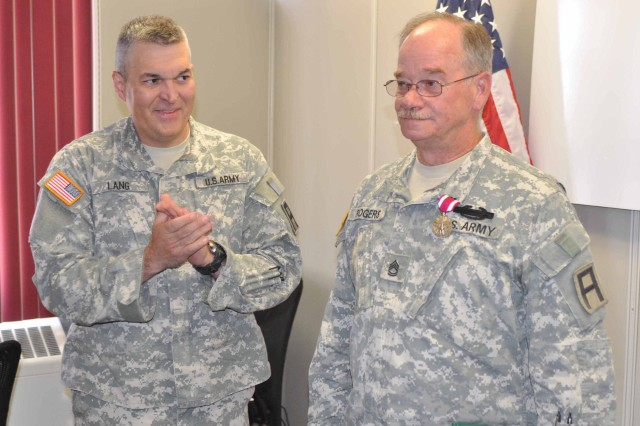Lt. Col Gary Lang, deputy commanding officer, 5th Armored Brigade, applauds Sgt. 1st Class Thomas Rogers, Headquarters and Headquarters Company, 5th Armored Brigade, after presenting him with the Meritorious Service Medal at Fort Bliss May 5.  Rogers is