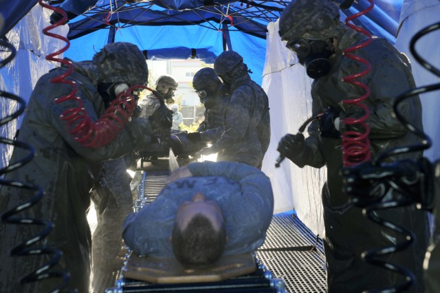 Soldiers of the 61st Chemical Company's decontamination platoon wash a contaminated Soldier with warm, soapy water to wash away any chemical, biological radiological or nuclear agents the casualty may have encountered during a mass casualty exercise