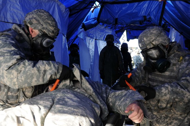 Soldiers of the 61st Chemical Company's decontamination platoon cut away a casualty's clothing before sending them through the wash tent during a mass casualty exercise in Elma, Wash., May 12. The clothing is cut off so the decontamination team