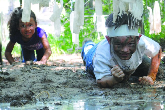 Kianna Williams, 5 (left), and Matthew Morris, 6, appear to have no worries of getting dirty as they low crawl through the mud at the Kid's Spur Ride May 7. The spur ride gave the children a peek into what Soldiers do. They went through a first aid