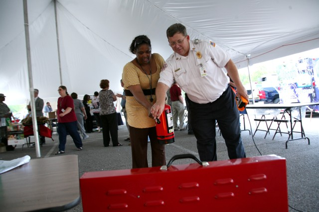 Robert Johnson, Redstone Arsenal fire prevention inspector, demonstrates to Yolanda Ellison how to aim a fire extinguisher during a joint command Safety Day that took place May 11 between the U.S. Army Space and Missile Defense Command/Army Forces
