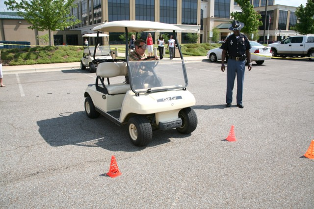 "Mark McClellan begins the drunk driving obstacle course with the Alabama Department of Public Safety's ""drunk goggles"" on while Trooper Curtis Summerville looks on during Safety Day, May 11. The event was co-hosted by the U.S. Army Space"