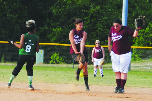 Lady Warriors shortstop Nina Middleton (center) and second baseman Kristi Allain (right) converge on a ground ball as the team's centerfielder, Shanna Winter (background), looks on, while Lucky Laydeez Scheryl Zeno pulls into second base during play