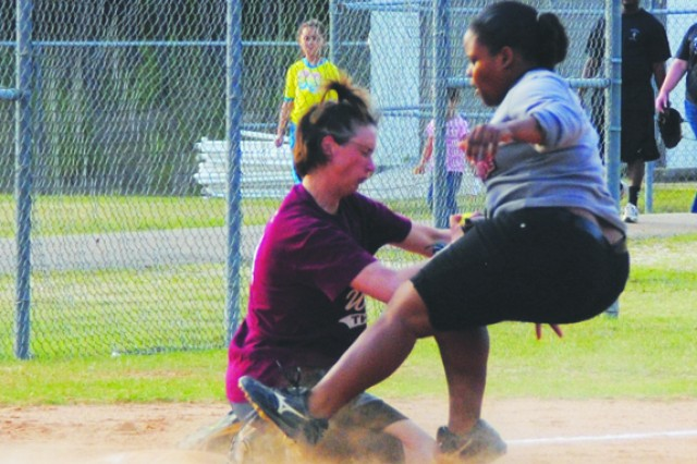 Lady Warrior thirdbaseman Lindsey Gregory (left) tags out Shemika Jackson of Lucky Laydeez on a close play at third base.