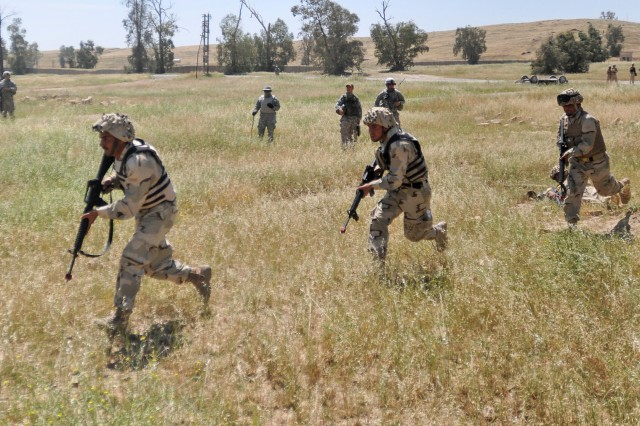 Iraqi soldiers from 3rd Company, 2nd Battalion, 9th Brigade, 3rd Iraqi Army Division conduct a cordon and search exercise during urban operations training at Ghuzlani Warrior Training Center, Iraq, May 12, 2011. U.S. Soldiers assigned to 1st Squadron,