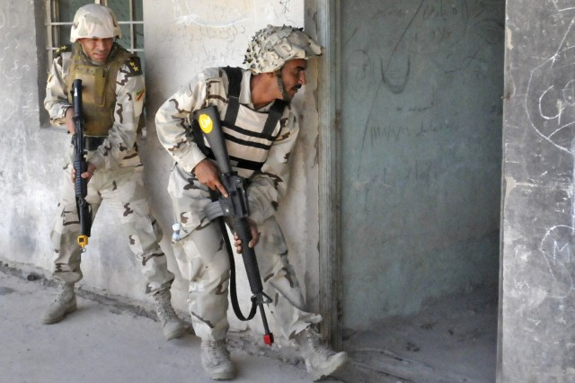 Soldiers assigned to 3rd Company, 2nd Battalion, 9th Brigade, 3rd Iraqi Army Division, prepare to enter and clear a room housing possible hostile suspects during a cordon and search exercise at Ghuzlani Warrior Training Center, Iraq, May 12, 2011. U.S.