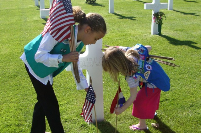Part of the tradition: Each year, the Saturday before the Memorial Day ceremony at Margraten is a busy day or preparation. Here, Girl Scouts join Boy Scouts and other local organization to ensure all 8, 301 graves are adorned with flags of the