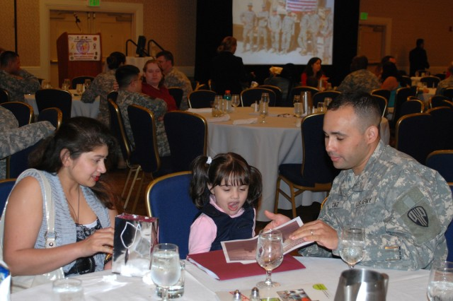 New York Army National Guard Staff Sgt. Jason Diaz, his wife Nisha (left) and daughter Thalia, 4, of Peekskill, N.Y., discuss scheduled activities during the 442nd Military Police Company 30-day Yellow Ribbon Reintegration event, May 14, 2011, at the