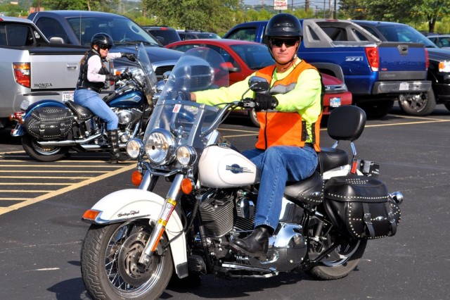 Command Sgt. Maj. Neil Ciotola, wearing his signature orange safety vest, is ready to ride. Ciotola rides his motorcycle to and from work every day. ""