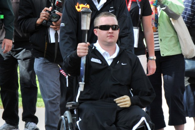 The Army team torchbearer, Pfc. Joshua Bullis, who will compete in the standing and prone rifle shooting competitions, leads the Army team during the opening ceremony.