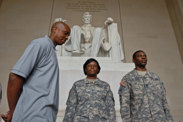Sgt. 1st Class LaTonya Terry-Matthews, left, and Cpt. Damien Butler stand at attention during the reading of the call to orders that announced her promotion to sergeant first class during a ceremony at the Lincoln Memorial in Washington D.C. May