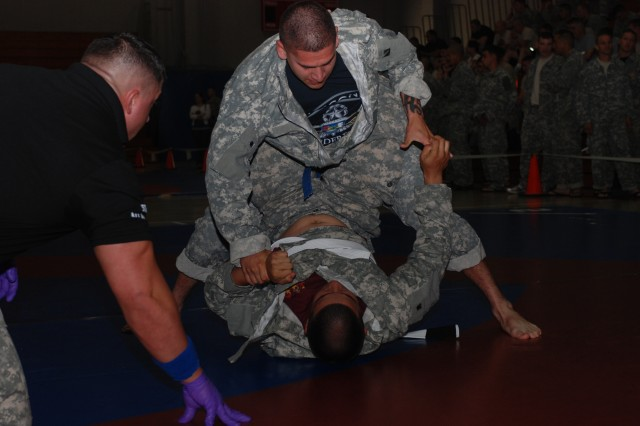 Paratroopers grapple for supremacy during a Modern Army Combatives Match at Ritz-Epps Gym. Blue and White belts were used to distinguish fighters. Referees wore matching wristbands so they could easily signal when fighters scored points. The six-minute