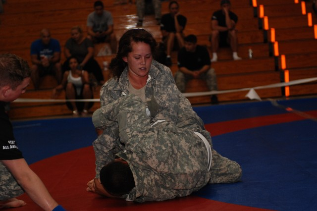 Pvt. Tiffany M. Warren, a Heavy Equipment Mechanic with Headquarters and Headquarters Company, 508th Special Troops Battalion, 4th Brigade Combat Team fights to force a submission from her opponent. In the semi-finals, fighters were forced to achieve a