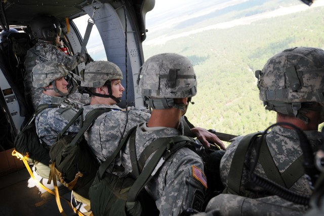 Paratroopers assigned to 1st Battalion, 504th Parachute Infantry Regiment, 1st Brigade Combat Team, sit on the edge of a UH-60 Blackhawk before conducting a static line jump on May 16. These soldiers make up part of the 1/504th PIR's team for the