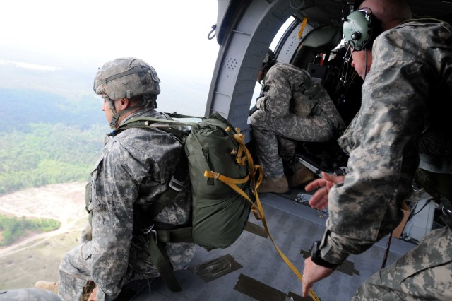 A Paratrooper assigned to 1st Battalion, 504th Parachute Infantry Regiment, 1st Brigade Combat Team, pushes off the edge of a UH-60 Blackhawk during a static line jump on May 16. He and seven other soldiers make up the 1/504th PIR's team for the