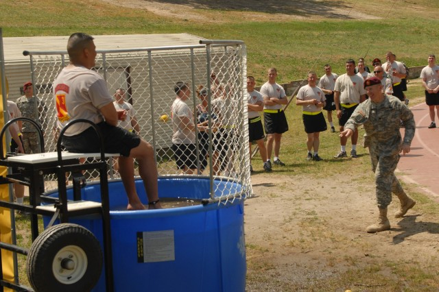 Lt. Col. Thomas Ham, commander, 3rd Battalion, 27th Field Artillery Regiment (HIMARS), throws a ball to try and dunk Maj. John Zeigler, executive officer, 3rd Bn., 27th FAR, at a regimental picnic May 17 on Fort Bragg, NC. The picnic was held as part of