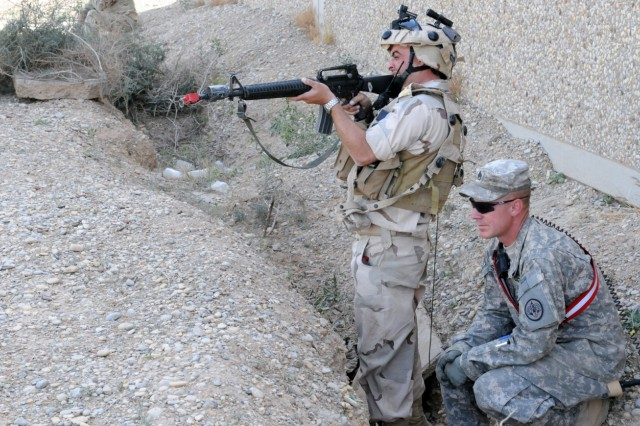 AN NUMANIYAH TRAINING BASE, Iraq - Staff Sgt. Ronnie Schooley, a cavalry scout with Troop F, 2nd Squadron, 3rd Armored Cavalry Regiment and a native of Ponca City, Okla., watches as an Iraqi Soldier engages enemies during training at the An Numaniyah