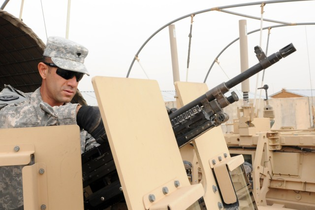 DIWANIYAH, Iraq - Spc. Cesar Nunez, an armored vehicle crewman with Company M, 3rd Squadron, 3rd Armored Cavalry Regiment, originally from Los Angeles, readies his M240B machine gun before a quick reaction force mission on Forward Operating Base Endeavor