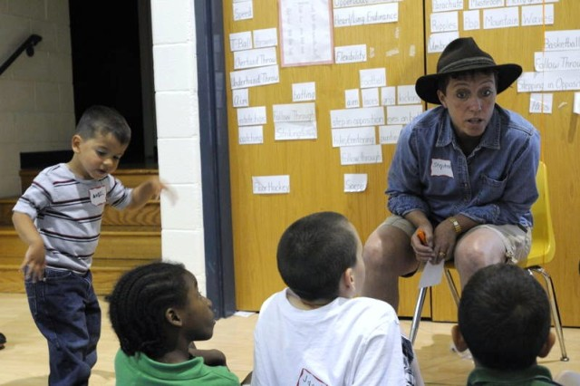 Stephenie Palmer, (right) the 7th Sustainment Brigade Family Readiness Support Assistant, leans in to listen to a comment from a child about what it's like to experience change. Military children had the opportunity to enjoy Tell Me A Story the