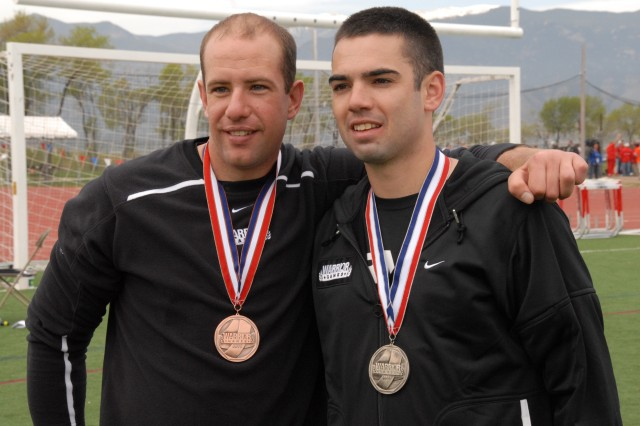 Robert Laux (left) and Kenny Griffith smile after medaling in the 100-meter dash for upper body amputee and limb dysfunction category during the 2011 Warrior Games Track and Field competition, Colorado Springs, Colo.