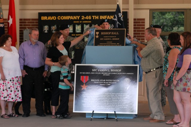 Sgt. 1st Class Jason Bishop's family helps unveil the plaque that will mark the barracks named in his honor.