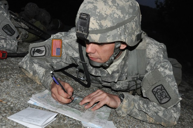 Staff Sgt. John Jestis, the 94th Military Police Battalion senior medic, plots grid coordinates during night land navigation training at Warrior Base, South Korea May 12, 2011. Jestis and other Soldiers from across South Korea gathered at Warrior Base to