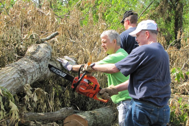 Lt. Gen. Bill Phillips, principal military deputy to the assistant Secretary of the Army for Acquisition, Logistics and Technology, operates the chain saw while Rev. David Tubbs, left, steadies the trunk and David Bonwit, in background, cuts other parts