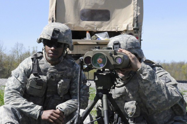 Staff Sgt. Cameron Neal, left, and Pvt. Troy Gromley, both with 2nd Battalion, 14th Infantry Regiment, observe where an artillery round impacted the ground during a field artillery exercise May 11 at Fort Drum's Outpost 4. The four-day exercise was