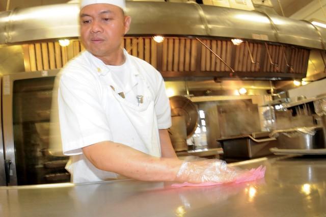 Spc. Avelino Arizapa sanitizes a table after using it to prepare enchiladas.
