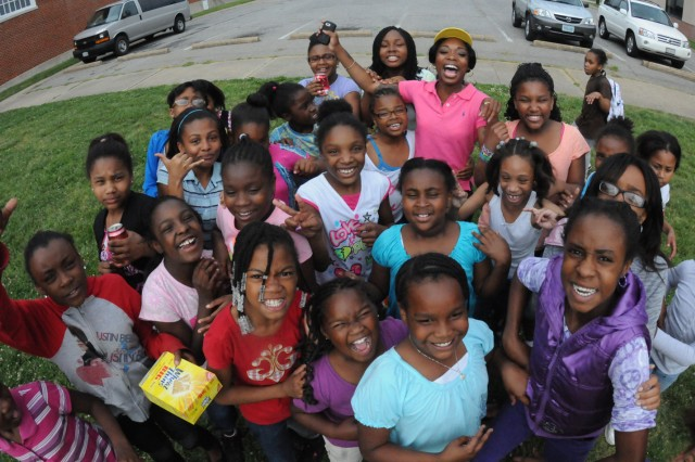 Spc. Erica Titues-Cepin (top, pink shirt) poses with the many young girls who seem to enjoy her company at the Boys and Girls Club in Hopewell.