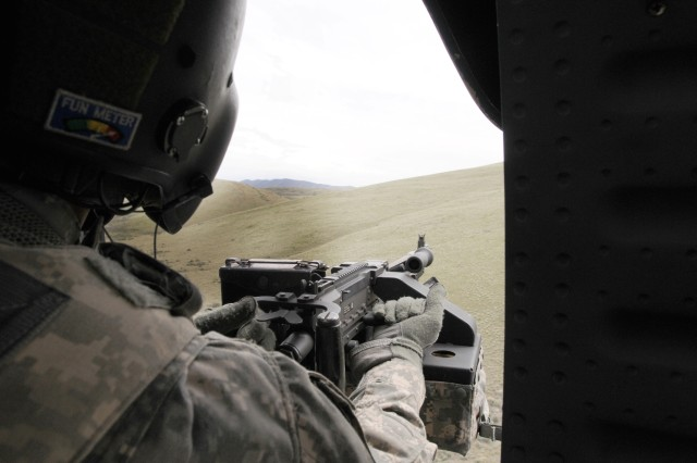 Sgt. 1st Class Jon maple, UH-60 Black Hawk crew chief, charges his weapon and prepares to fire at targets during a live fire exercise at Yakima Training Area, May 11.